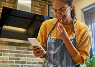 Woman cooking and looking at phone